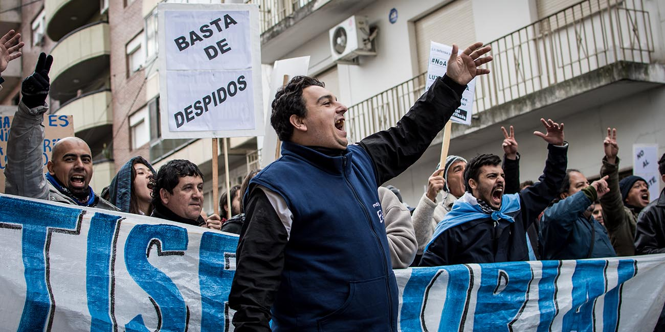 """Protesters against Mauricio Macri under a sign saying """"no more job cuts!"""""""