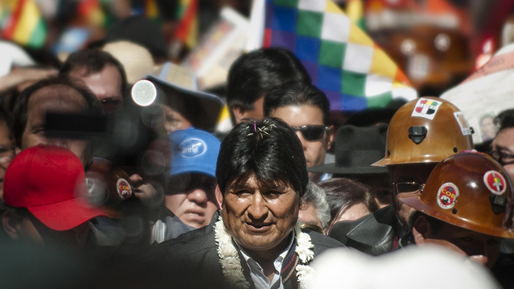 Bolivian president Evo Morales walks towards the camera amongst a throng of supporters