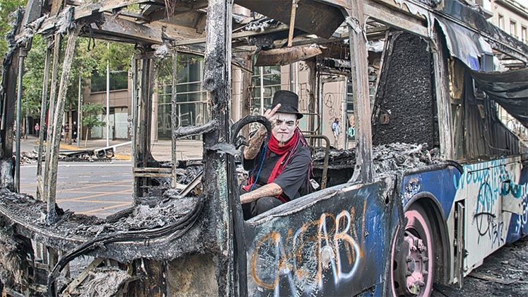 A protester in Santiago sits inside a burnt-out bus and raises his middle finger to the camera