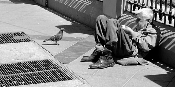 An elderly man lying in the street exchanges a glance with a pigeon at his side