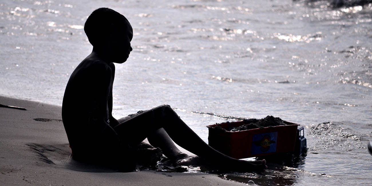 Silhouette of a boy playing in the sand on Colombia's Caribbean coast
