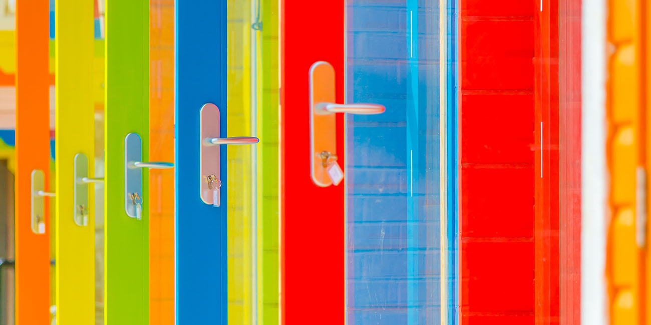 A series of brightly coloured open doors with the keys in the locks