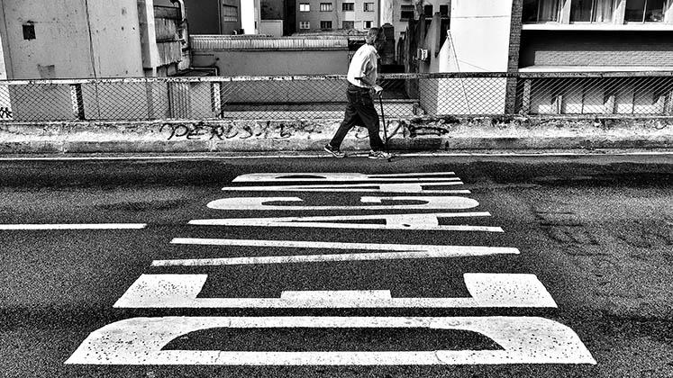 Un hombre mayor camina con bastón en Sao Paulo al lado de una señal que dice 'despacio'