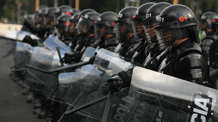 Heavily armoured ESMAD riot police stand in formation in Bogotá