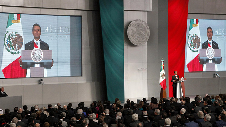 Mexican president Enrique Peña Nieto makes a speech in front of two big screens