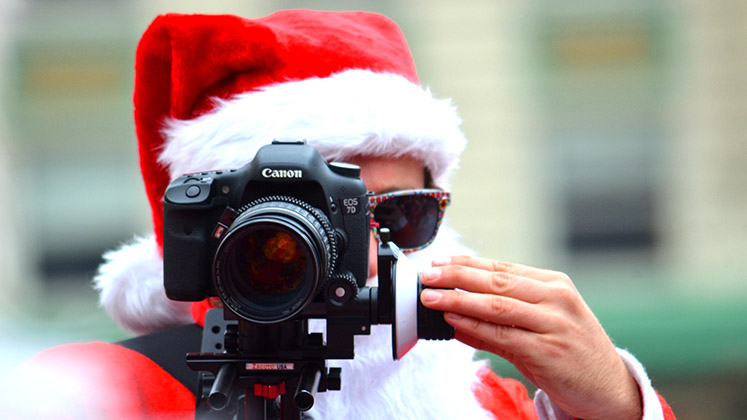 A man in a Santa outfit looks through a camera on a tripod