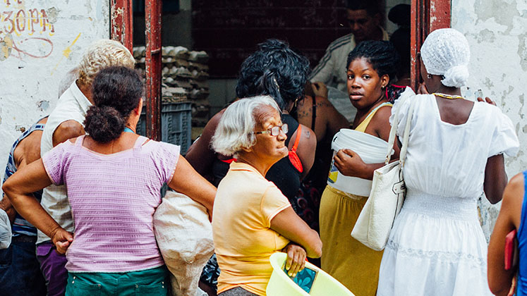 A group of women in Havana, Cuba, wait around the entrance of a food dispensary