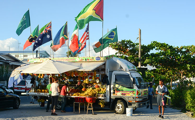 A fruit stand in Georgetown beneath the Guyanese flag