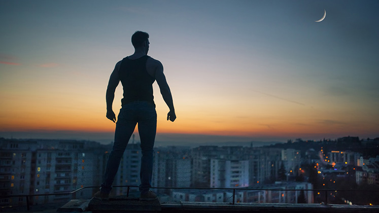 A man standing on a ledge surveys a cityscape at sunset