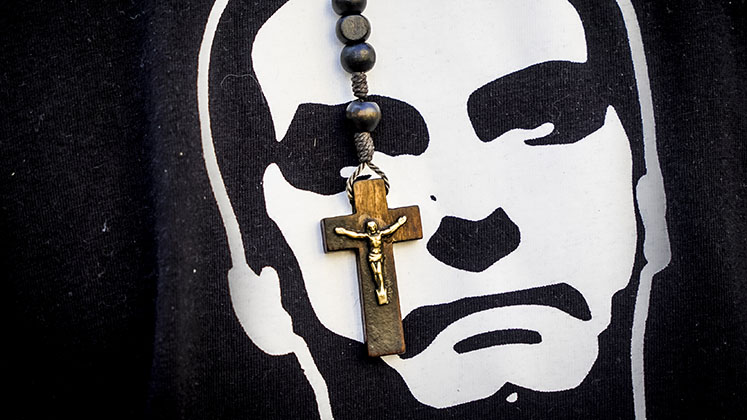 A small wooden crucifix hangs in front of a black-and-white likeness of Brazilian president Jair Bolsonaro