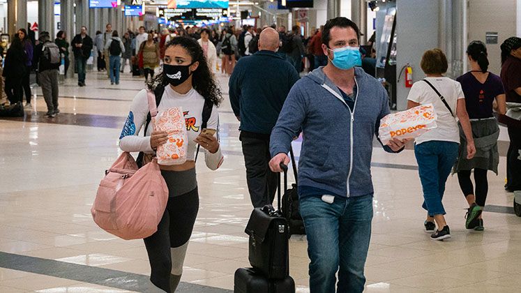 Two passengers at Atlanta International Airport walk through the terminal in face masks, 6 March 2020, as the coronavirus spreads throughout the United States