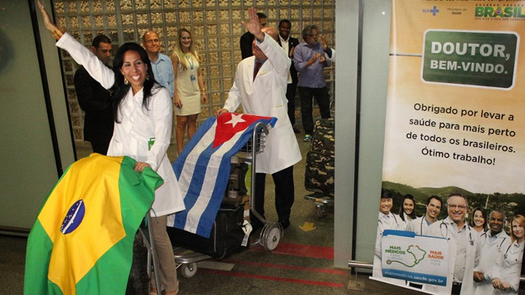 Cuban doctors arrive in Brazil with their two countries' flags draped over luggage trolleys