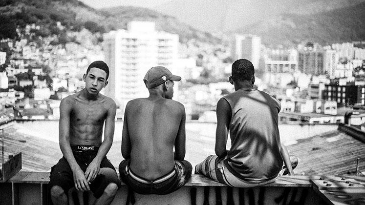 Three teenage boys in the Telerj favela sit on a wall overlooking Rio de Janeiro, Brazil
