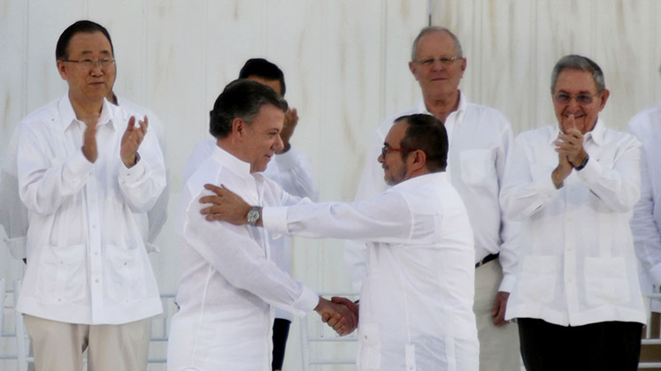 Colombian president Juan Manuel Santos and FARC's Rodrigo Londoño Echeverri (Timochenko) shake hands at signing ceremony for the peace deal in Havana