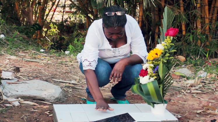 A mourning relative places her hand on the grave of a lost loved-one in Barrancabermeja, Colombia