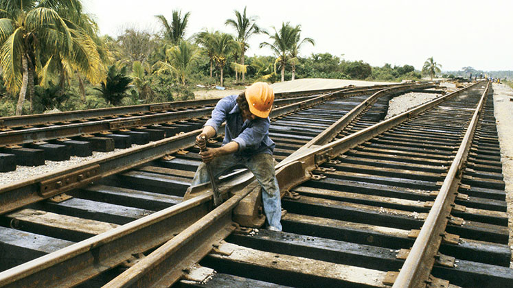 A rail worker strains to fix two diverging tracks in Mexico