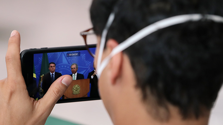 A masked journalist films Paulo Guedes and Jair Bolsonaro on his smartphone during a press conference in April 2020