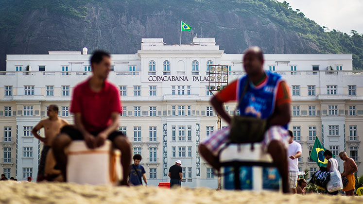 Two street vendors take a break in front of the Copacabana Palace Hotel, Rio de Janeiro, Brazil