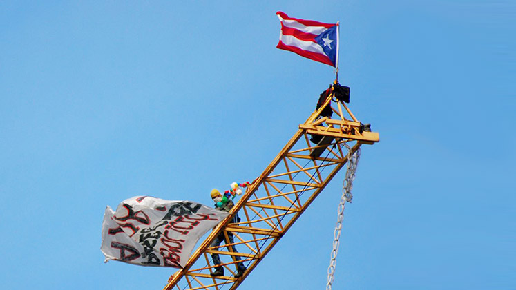 A protester flies the Puerto Rican flag from a crane over San Juan in 2007