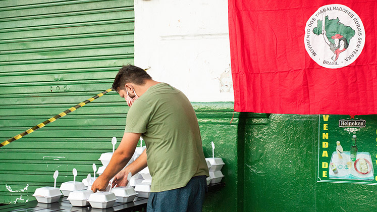 A volunteer prepares lunch boxes for homeless people in Recife, Brazil, during the coronavirus crisis