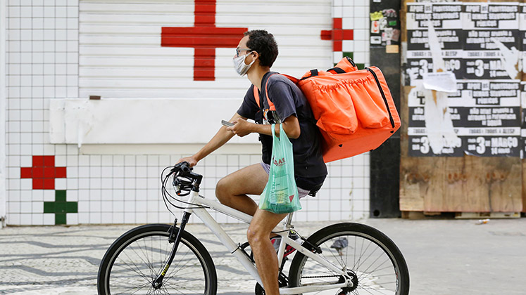 A delivery rider cycles past a red cross while checking an app in Sao Paulo, Brazil