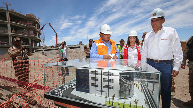 Peru's President Vizcarra examines a scale model of a university development on a construction site