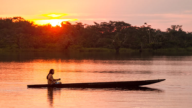 A member of an indigenous tribe in the Ecuadorian Amazon rows across the sunset
