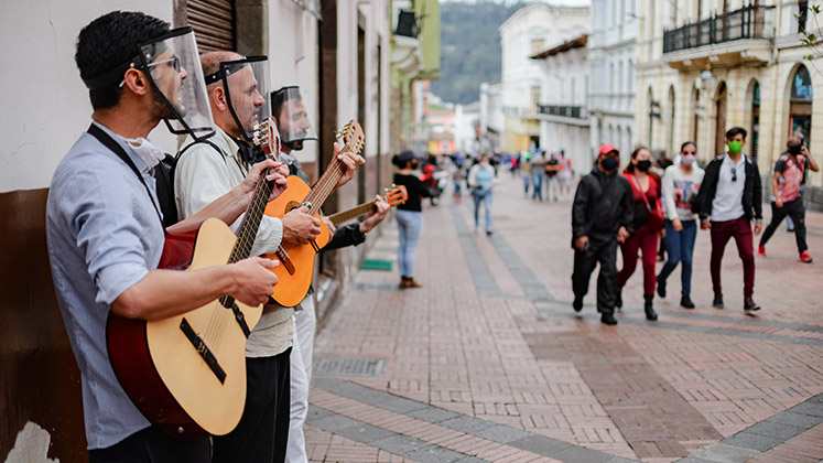Three buskers in protective face masks play to passers-by in Quito's Centro Historico