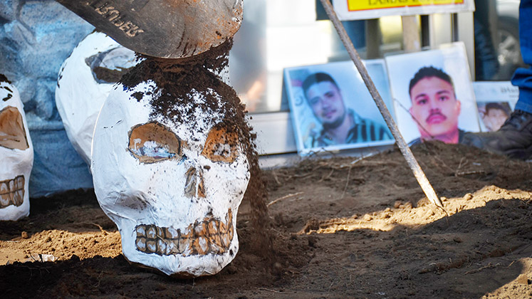 Soil is shovelled over a model skull as part of a protest against enforced disappearances in Mexico