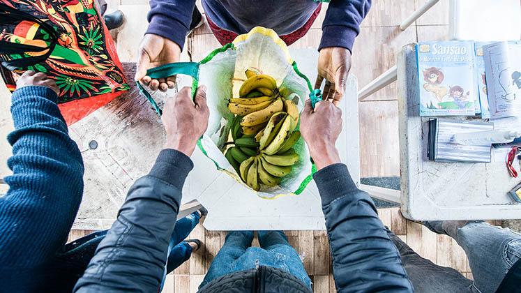 A man hands over a bag of bananas during a Campo-Favela sale
