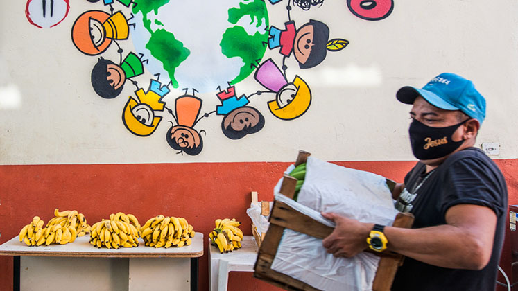 A member of the Campo Favela project carries food past a table full of bananas