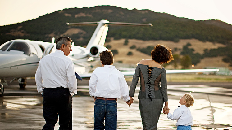 A wealthy family walks along the runway towards a private jet