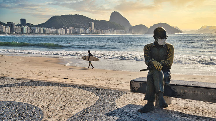A surfer walks out of the water on a Rio beach behind a mask-wearing statue of poet Carlos Drummond de Andrade
