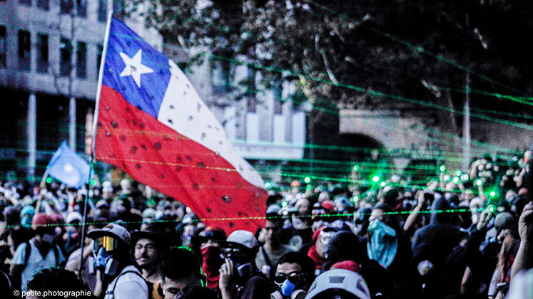 The Chilean flag waves above protesters in Santiago, Chile