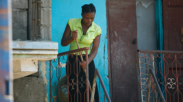 A domestic worker sweeps the porch in Haiti