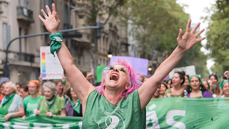 A pink-haired woman marching for legalisation of abortion in Argentina throws her arms towards the sky