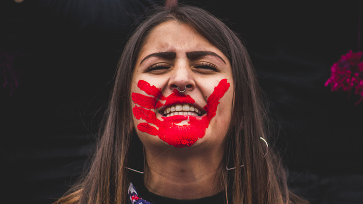 A woman in Santiago, Chile, protests for women's rights with a bloody hand print painted over her mouth