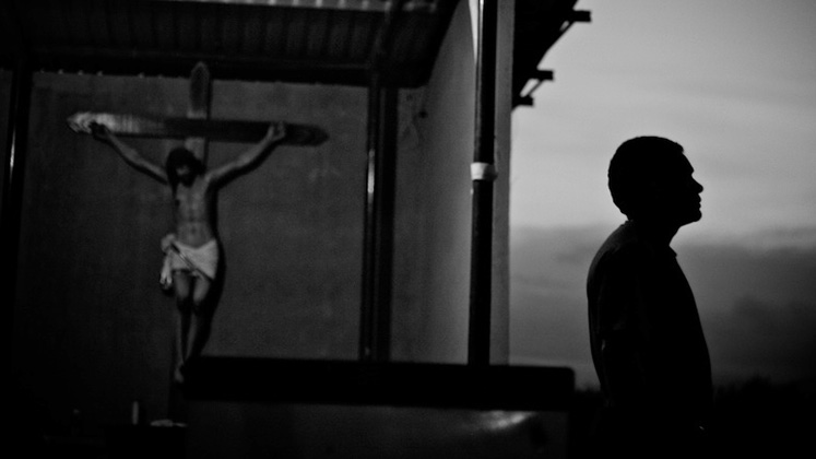 A silhouetted man looks into the distance at a migrant shelter in southern Mexico in front of a depiction of Christ on the cross