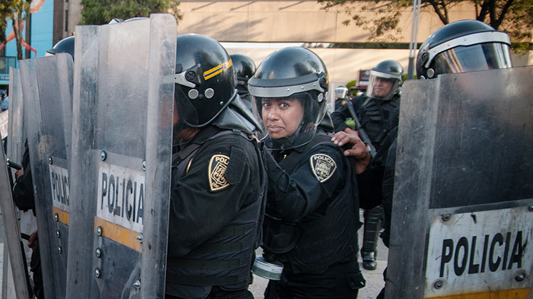A policewoman behind a line of riot shields in Mexico City looks into the camera