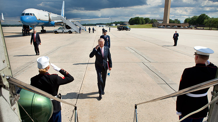 Joe Biden salutes as he enters a waiting vehicle from an airport runway