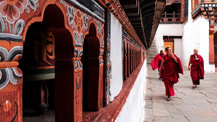 Three monks in red robes walk past prayer wheels in Bhutan