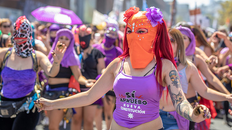 """A masked woman dances in a """"Vote Yes"""" t-shirt during a demonstration in Santiago, Chile"""