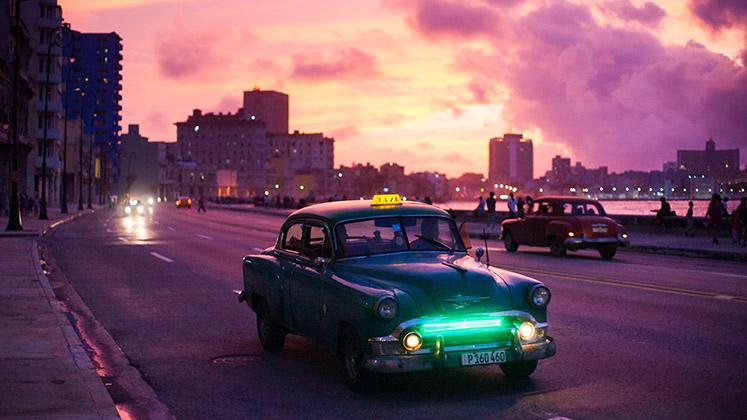 A taxi rolls through Havana at twilight