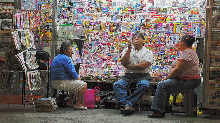 Three people chat beneath the fluorescent lights of a newsstand in Aguascalientes, Mexico