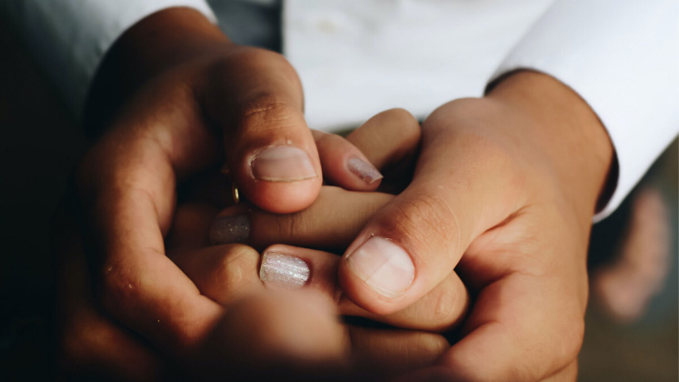 A pair of hands holding another person's hand