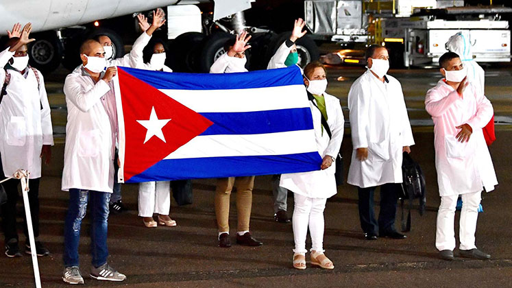 Cuban medical personnel hold up the national flag and wave as they arrive in South Africa in April 2020