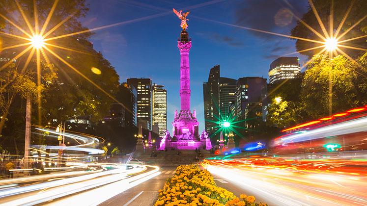 Cars stream around the illuminated Independence Angel on Mexico City's Paseo de la Reforma