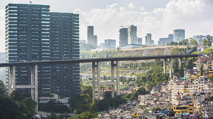 A tower of new flats beside a hillside barrio in Mexico City