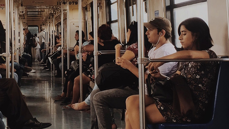 A woman listens to music while travelling on a train in Monterrey, Mexico