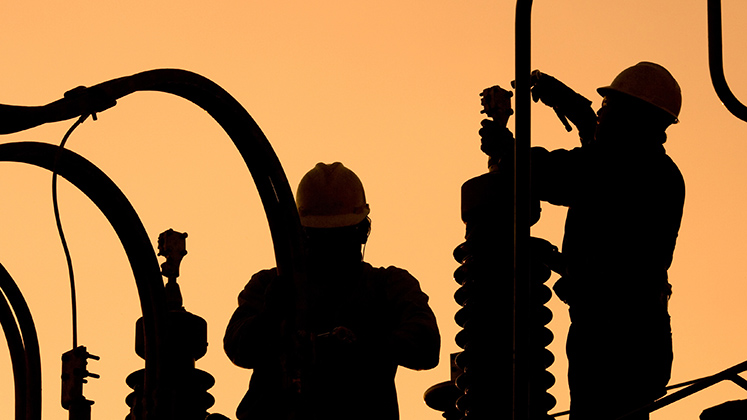 Workers setting up an electricity substation in Santiago de Chile as the sun goes down